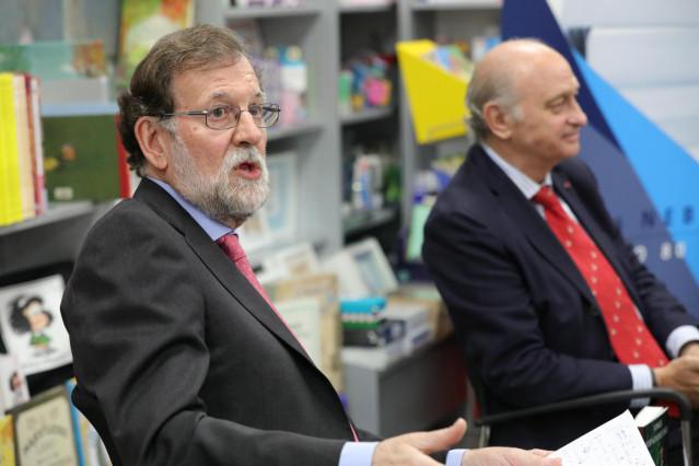 El expresidente del Gobierno Mariano Rajoy (i), y el exministro de Interior y miembro del PP, Jorge Fernández Díaz